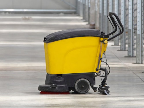 Yellow commercial floor scrubber cleaning a facility